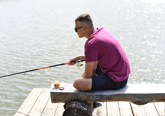 Jonge visser zittend op houten pier vissen in het meer