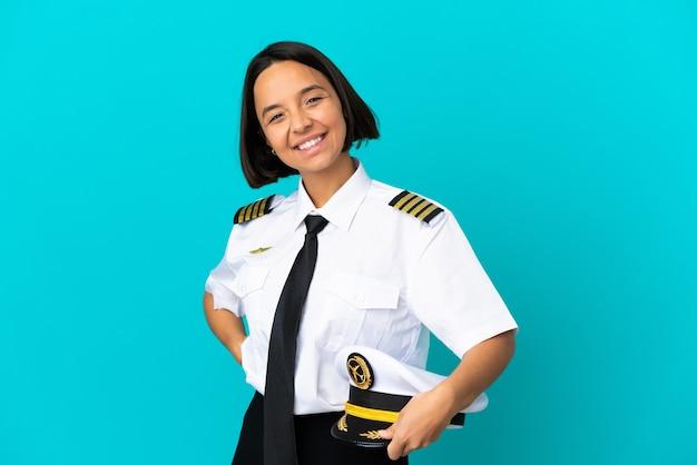 Jonge vliegtuigpiloot over geïsoleerde blauwe achtergrond applaudisseren