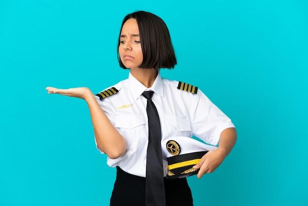 Jonge vliegtuigpiloot over geïsoleerde blauwe achtergrond die copyspace met twijfels houdt