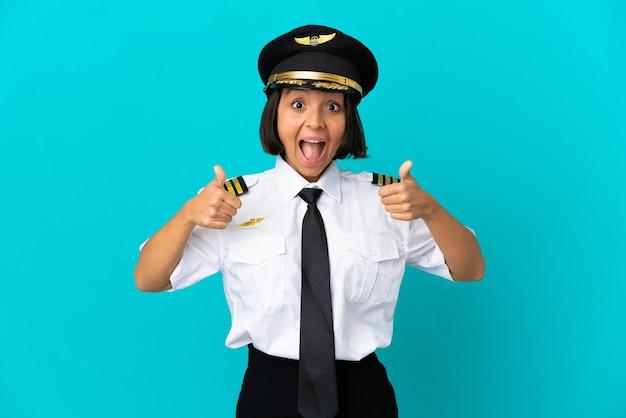 Jonge vliegtuigpiloot over geïsoleerde blauwe achtergrond die een duim omhoog gebaar geeft