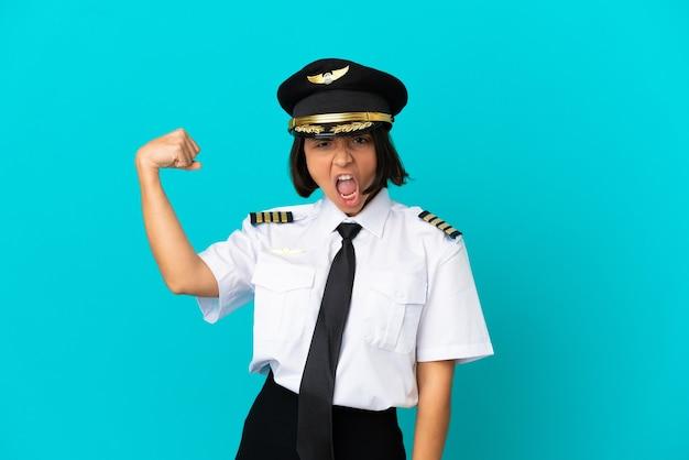 Jonge vliegtuigpiloot over geïsoleerde blauwe achtergrond die een overwinning viert