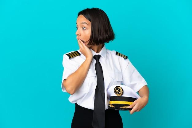 Jonge vliegtuigpiloot over geïsoleerde blauwe achtergrond die een verrassingsgebaar doet terwijl hij naar de zijkant kijkt