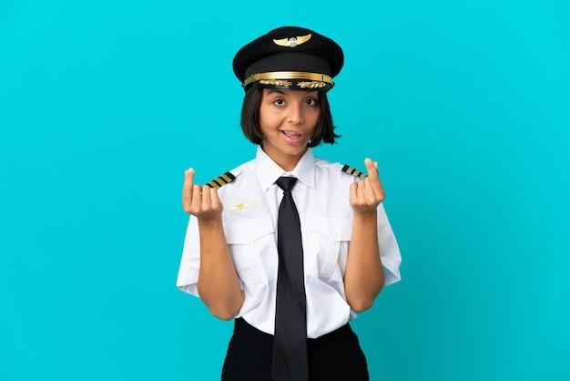 Jonge vliegtuigpiloot over geïsoleerde blauwe achtergrond die geldgebaar maakt
