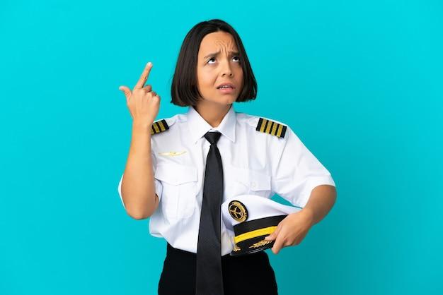 Jonge vliegtuigpiloot over geïsoleerde blauwe achtergrond die het gebaar van waanzin maakt en vinger op het hoofd legt