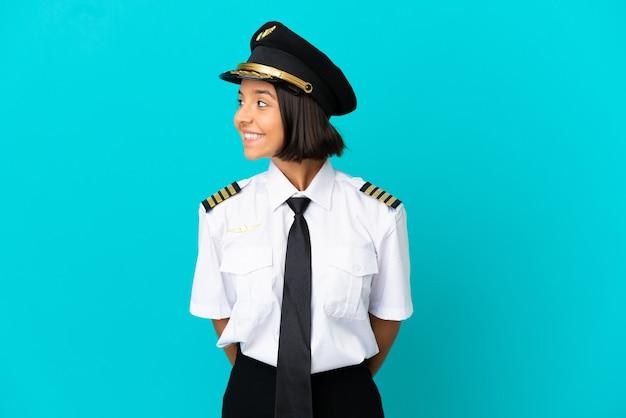 Jonge vliegtuigpiloot over geïsoleerde blauwe achtergrond die kant kijkt