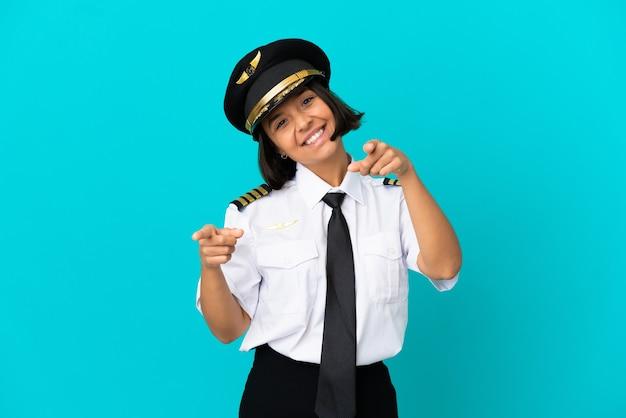 Jonge vliegtuigpiloot over geïsoleerde blauwe achtergrond die naar voren wijst met gelukkige uitdrukking