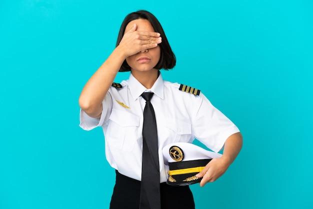 Jonge vliegtuigpiloot over geïsoleerde blauwe achtergrond die ogen bedekt door handen