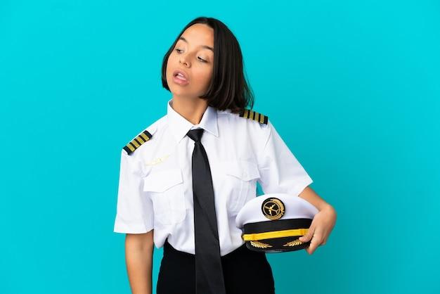 Jonge vliegtuigpiloot over geïsoleerde blauwe achtergrond die twijfels heeft terwijl hij opzij kijkt looking
