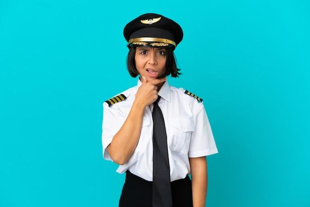 Jonge vliegtuigpiloot over geïsoleerde blauwe achtergrond die twijfels heeft