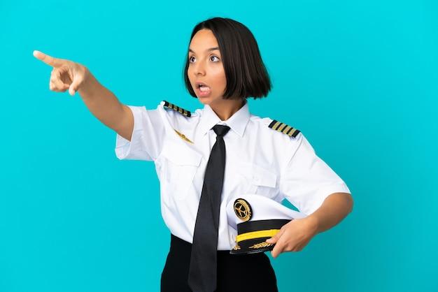 Jonge vliegtuigpiloot over geïsoleerde blauwe achtergrond die weg wijst