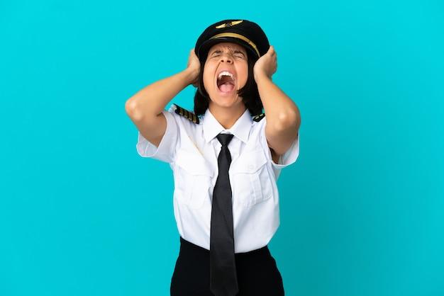 Jonge vliegtuigpiloot over geïsoleerde blauwe achtergrond gestrest overweldigd