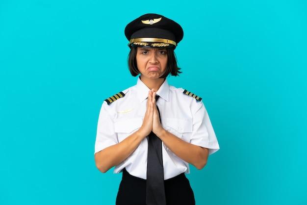 Jonge vliegtuigpiloot over geïsoleerde blauwe achtergrond houdt de palm bij elkaar. persoon vraagt om iets