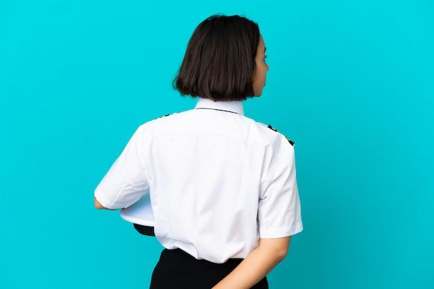 Jonge vliegtuigpiloot over geïsoleerde blauwe achtergrond in achterpositie en terugkijkend