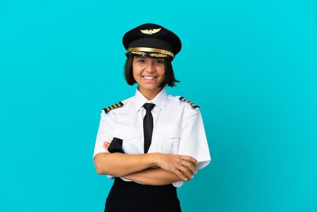 Jonge vliegtuigpiloot over geïsoleerde blauwe achtergrond met gekruiste armen en vooruitkijkend