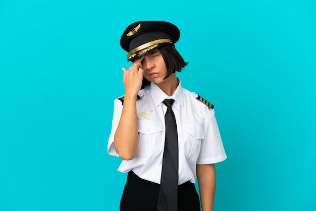 Jonge vliegtuigpiloot over geïsoleerde blauwe achtergrond met hoofdpijn