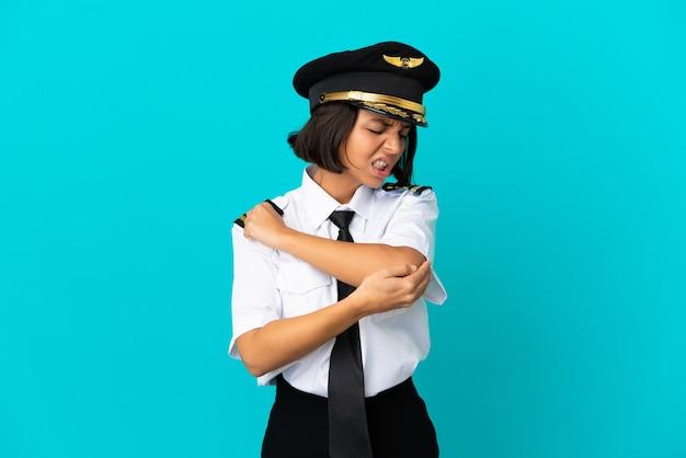 Jonge vliegtuigpiloot over geïsoleerde blauwe achtergrond met pijn in elleboog