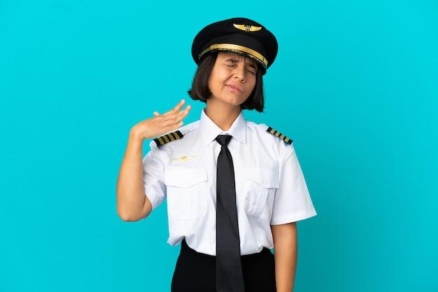Jonge vliegtuigpiloot over geïsoleerde blauwe achtergrond met vermoeide en zieke uitdrukking