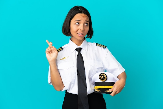 Jonge vliegtuigpiloot over geïsoleerde blauwe achtergrond met vingers die kruisen en het beste wensen