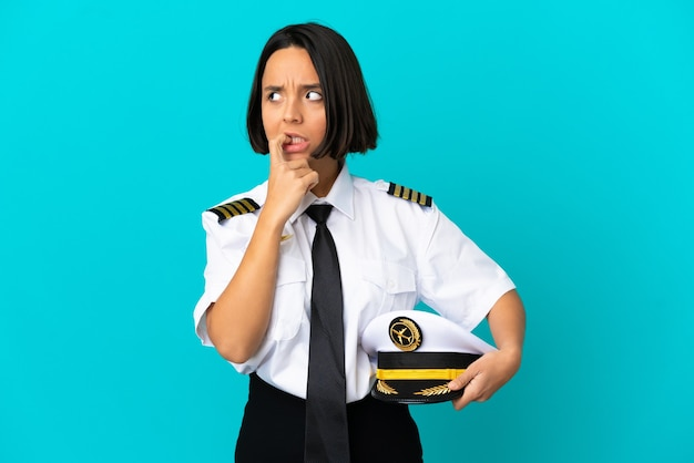 Jonge vliegtuigpiloot over geïsoleerde blauwe achtergrond nerveus en bang