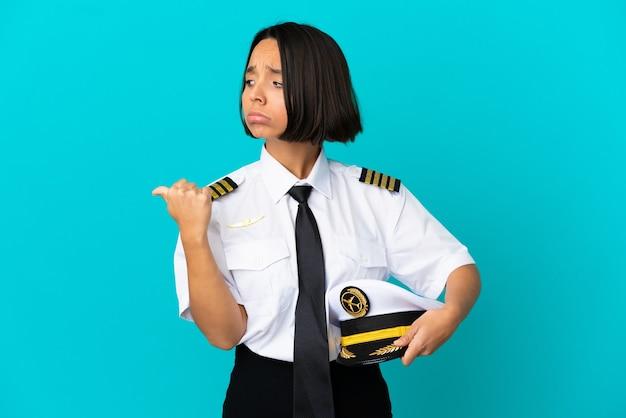 Jonge vliegtuigpiloot over geïsoleerde blauwe achtergrond ongelukkig en wijzend naar de zijkant