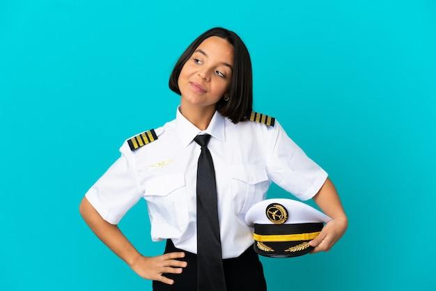 Jonge vliegtuigpiloot over geïsoleerde blauwe achtergrond terwijl hij glimlacht
