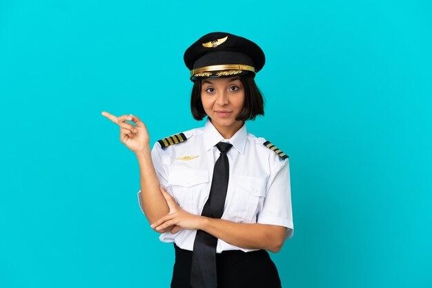 Jonge vliegtuigpiloot over geïsoleerde blauwe achtergrond wijzende vinger naar de zijkant