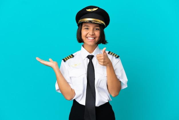 Jonge vliegtuigpiloot over geïsoleerde blauwe muur die copyspace denkbeeldig op de palm houdt om een advertentie in te voegen en met duimen omhoog