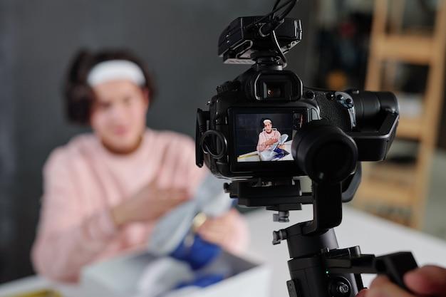 Jonge vlogger in vrijetijdskleding toont nieuwe sneakers en beschrijft ze op het display van een digitale videocamera
