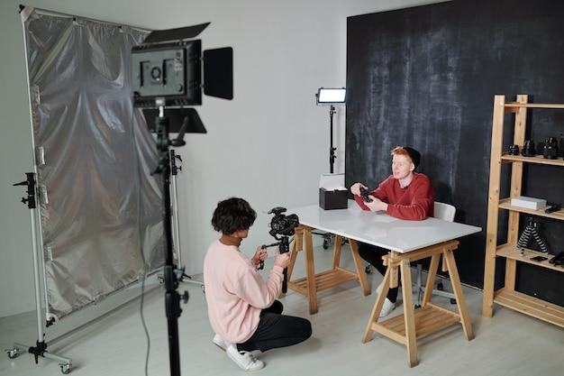 Jonge vlogger vertelt over nieuwe fotoapparatuur zittend bij bureau voor operator met videocamera