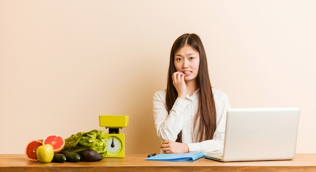 Jonge voedingsdeskundige chinese vrouw die met haar laptop bijt vingernagels, nerveus en zeer angstig.