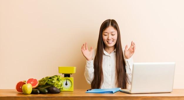 Jonge voedingsdeskundige chinese vrouw die met haar laptop het blije lachen veel werkt. geluk concept.