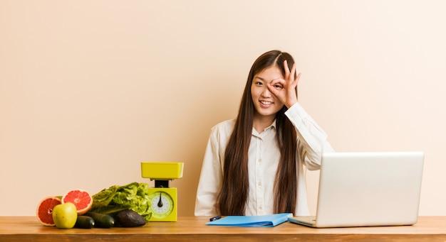 Jonge voedingsdeskundige chinese vrouw die met haar laptop opgewonden het houden van ok gebaar aan oog werkt.