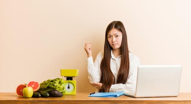 Jonge voedingsdeskundige chinese vrouw die met haar laptop wat betreft achterhoofd werkt, en een keus denkt maakt.