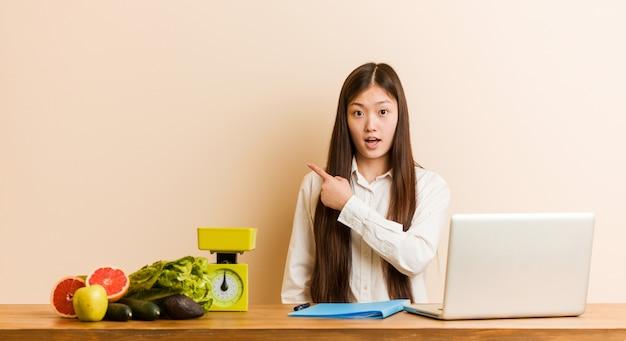 Jonge voedingsdeskundige chinese vrouw die met haar laptop werkt die aan de kant richt