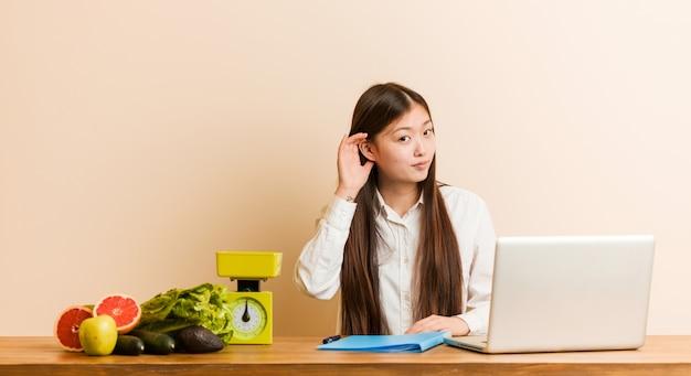Jonge voedingsdeskundige chinese vrouw die met haar laptop werkt die aan het luisteren van een roddel probeert.