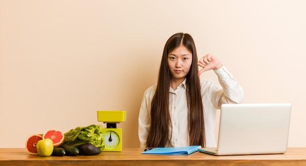 Jonge voedingsdeskundige chinese vrouw die met haar laptop werkt die een afkeergebaar tonen, duimen neer. meningsverschil concept.