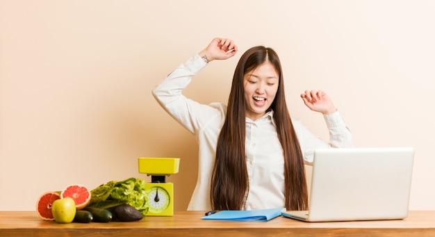 Jonge voedingsdeskundige chinese vrouw die met haar laptop werkt die een speciale dag viert, sprongen en wapens met energie opheft.