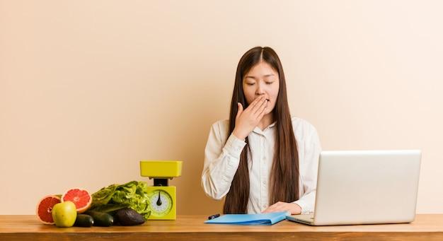Jonge voedingsdeskundige chinese vrouw die met haar laptop werkt die een vermoeid gebaar tonen die mond behandelen met hem hand.