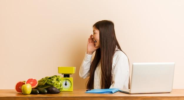 Jonge voedingsdeskundige chinese vrouw die met haar laptop werkt die en palm schreeuwt dichtbij geopende mond houdt.