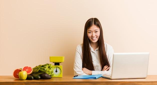 Jonge voedingsdeskundige chinese vrouw die met haar laptop werkt die en pret lacht heeft.