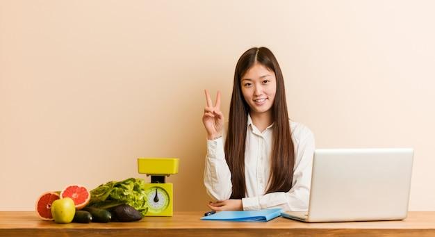 Jonge voedingsdeskundige chinese vrouw die met haar laptop werkt die nummer twee met vingers toont.