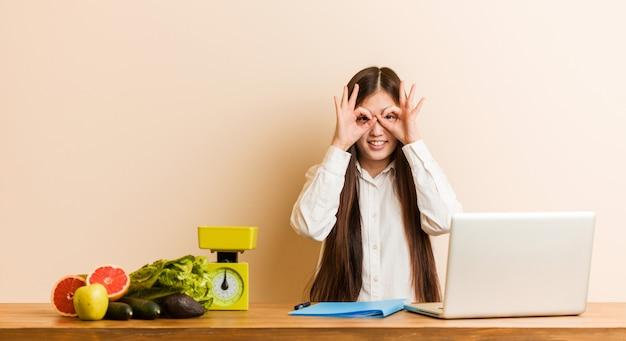 Jonge voedingsdeskundige chinese vrouw die met haar laptop werkt die ok teken over ogen toont
