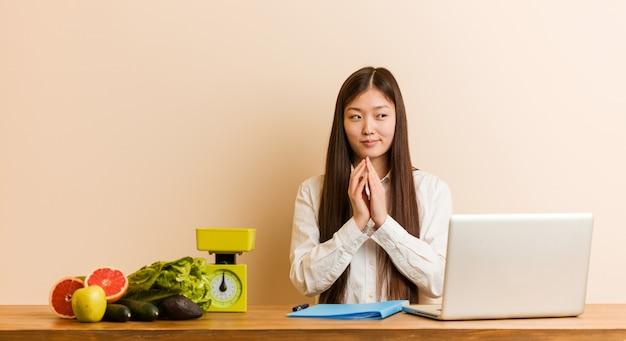 Jonge voedingsdeskundige chinese vrouw die met haar laptop werkt die plan in mening opmaakt, die een idee opzet.