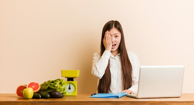Jonge voedingsdeskundige chinese vrouw die met haar laptop werkt die pret heeft die de helft van gezicht behandelt met palm.