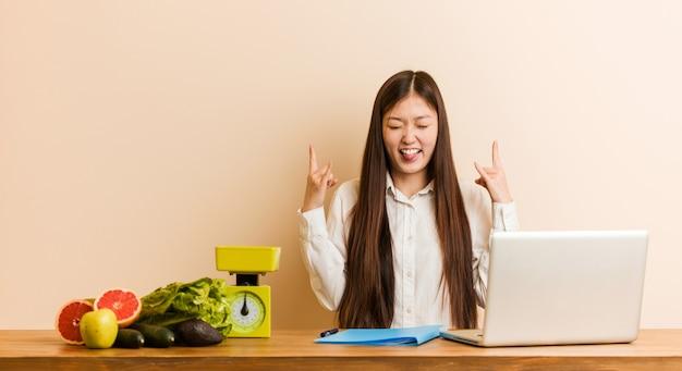 Jonge voedingsdeskundige chinese vrouw die met haar laptop werkt die rotsgebaar met vingers toont