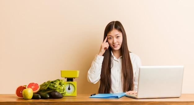 Jonge voedingsdeskundige chinese vrouw die met haar laptop werkt die tempel met vinger richt, het denken, concentreerde zich op een taak.