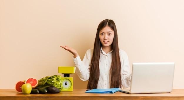 Jonge voedingsdeskundige chinese vrouw die met haar laptop werkt die tussen twee opties twijfelt.