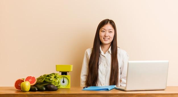 Jonge voedingsdeskundige chinese vrouw die met haar laptop werkt die van het dromen van doelstellingen en doelstellingen dromen