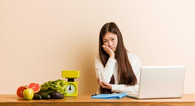 Jonge voedingsdeskundige chinese vrouw die met haar laptop werkt die zich verveelt, moe is en een relaxdag nodig heeft.