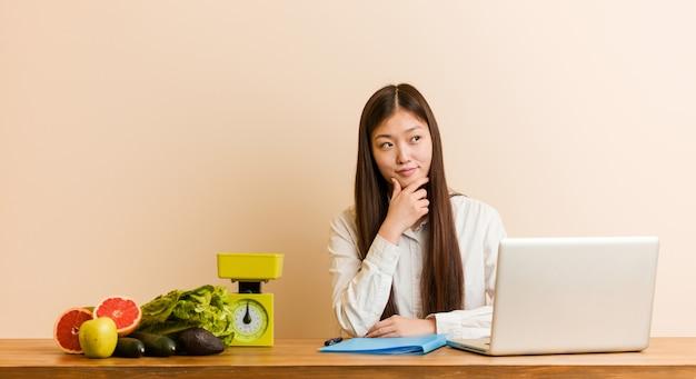 Jonge voedingsdeskundige chinese vrouw die met haar laptop werkt die zijdelings met twijfelachtige en sceptische uitdrukking kijkt.
